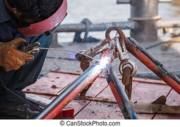 Man welding steel on the part of fishing boat at the harbor...