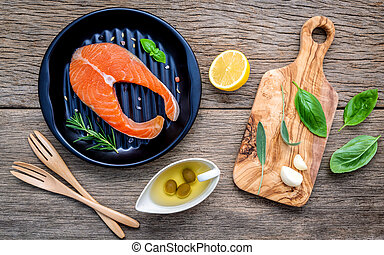 Raw salmon fillet in the black plate with ingredients olive...