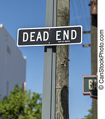 'Dead End' sign on a wooden post