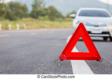 Red emergency stop sign and broken car on the road - Red...