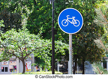 Blue bicycle lane sign with trees background