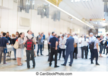 Abstract blurred people socializing during coffee break at...