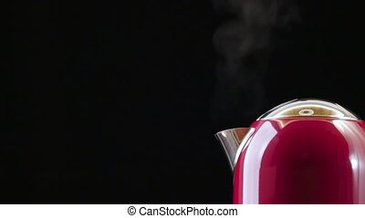 Boiling red kettle on the black background