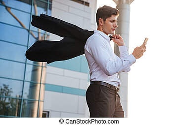 Businessman holding mobile phone walking with jacket over...