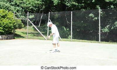 senior practice tennis serve - middle age senior man tennis...