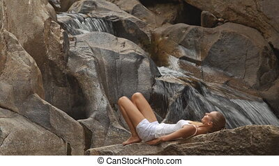 Blond Girl Lies down Does Back Bridge on Stone by Waterfall...
