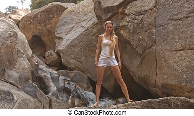 Blond Girl Does Side Bend Yoga Pose by Waterfall - blond...