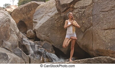 Closeup Blond Girl Stands in Yoga Tree Pose by Waterfall -...