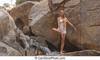 Blond Girl Stands in Yoga Tree Pose by Waterfall - blond...