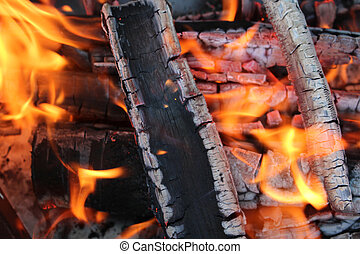 Flame - Charred wood and bright flames on dark background