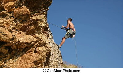 Climber Doing Down The Rope From A Cliff
