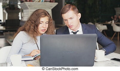 Man and woman with modern laptop work in cafe - Man and...