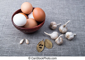 Chicken eggs and garlic and spices on the kitchen table on...