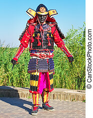 Man in samurai costume with a sharp deadly weapon in the...