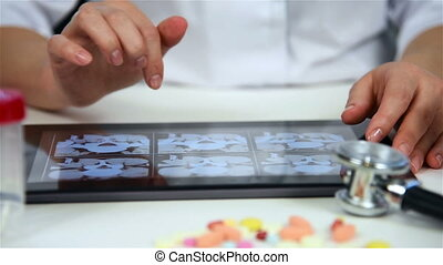 Doctor Examines An X-ray Of The Patient On Tablet