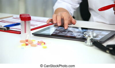 Doctor Examines An X-ray Images Of Patient On Digital Tablet