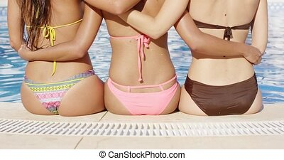 Three shapely woman in bikinis sitting arm in arm at the...