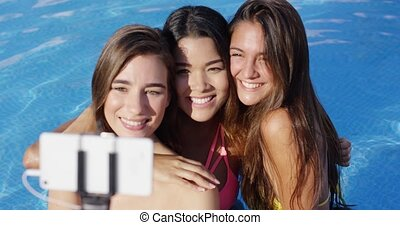 Three pretty young women posing for a selfie in the...