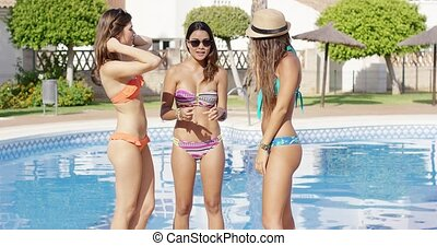 Three sexy trendy women in bikinis posing standing close...