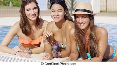 Three gorgeous friendly young women in bikinis relaxing in...
