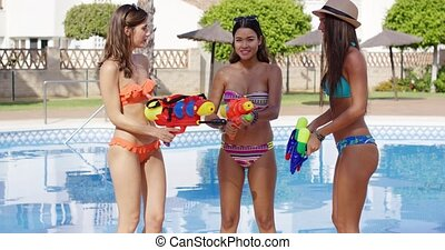 Women wearing colorful bikinis and playing with super...