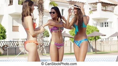 Three young women in bikinis standing outside in...
