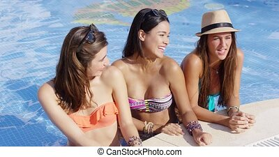 Three trendy woman relaxing at a pool together - Three...