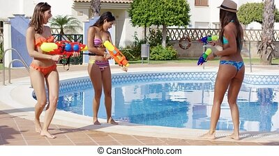 Three beautiful friends with water guns in bikinis play by...