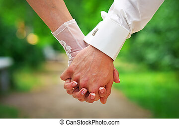 Couple holding hands. Two pairs of hands in love hold...