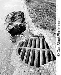 Girl looking down a manhole - girl looking down a manhole in...