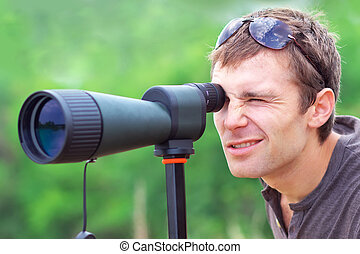 Man who is watching in spotting scope. Positive man looking...