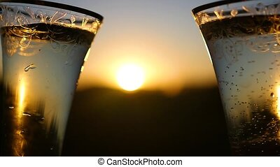 wine glasses clink at sunset closeup