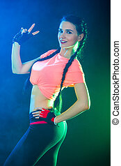 Sportive young woman between bright green and blue lights