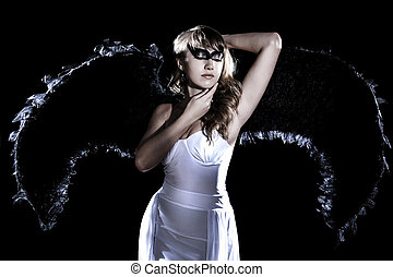 Beautiful young woman in a long white dress and with black...