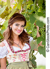 Beautiful young woman in traditional bavarian dress holding...