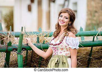 Beautiful woman in traditional bavarian dress against hay...