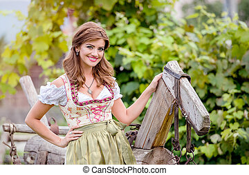 Woman in traditional bavarian dress sitting on wooden horse...