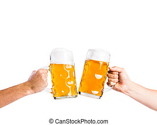 Two unrecognizable men clinking with beer mugs, studio shot...