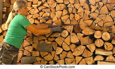 Young woman lays on chopped wood in the woodpile - Young...