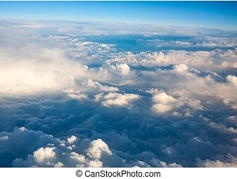 clouds top view from the window of an airplane flying in the...