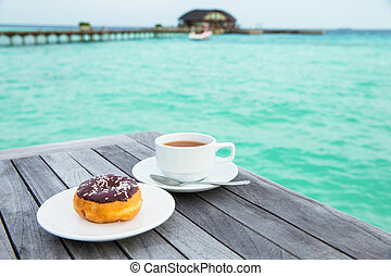 A cup of tea on table with sea at the background