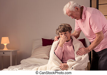 You should go to bed - Ill senior woman sitting on a bed and...