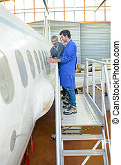 People studying aircraft fuselage