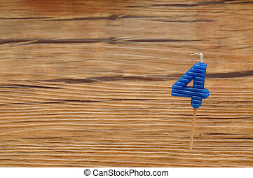 A birth day candle isolated on a wooden background Blue...