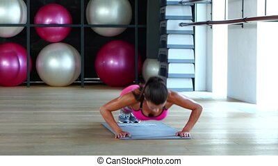 Woman in sportswear does push-ups in a gym, people training...