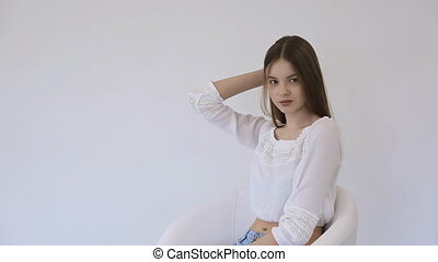 Young model sits in comfortable chair and practices in posing.