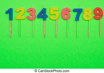 Birthday candles numbers 1 to 9 isolated on a green...