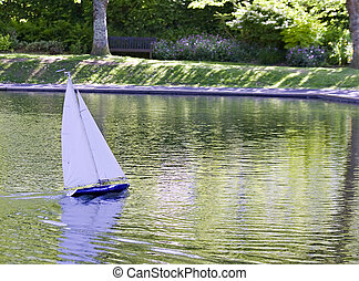 Remote control toy yacht sailing on a lake