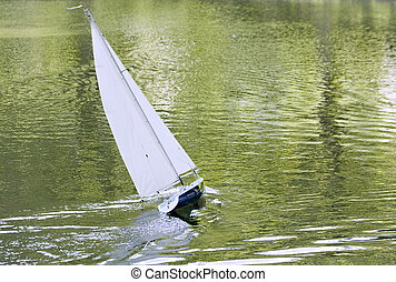 A radio control toy yacht sailing on a lake