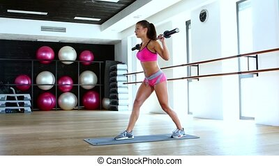 Woman and doing lunge with barbell and flexing muscles in...